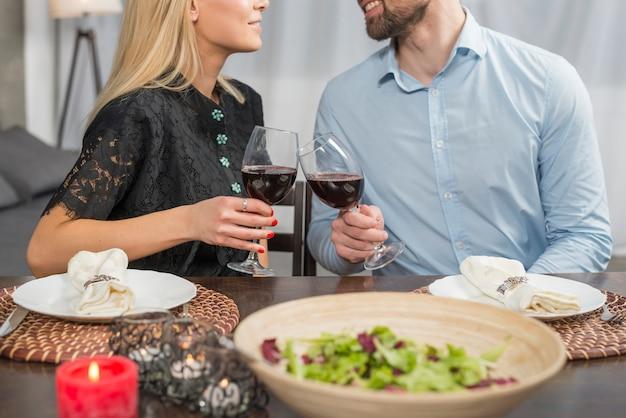 Glimlachende man en vrouw die glazen van drank klinken bij lijst met kom salade en platen Gratis Foto