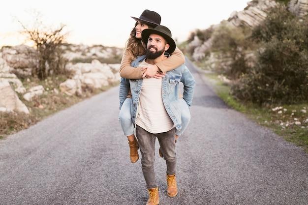 Glimlachende man en vrouw op een bergweg die weg kijken Gratis Foto