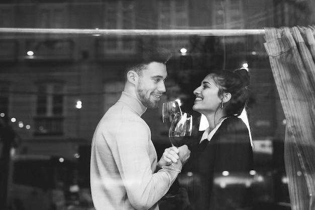 Glimlachende man en vrouwenholdingsglazen wijn in restaurant Gratis Foto