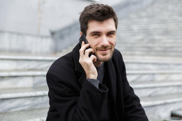 Glimlachende man gekleed in jas zittend aan de straat, praten op de mobiele telefoon Premium Foto