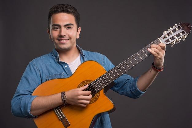 Glimlachende man gitaarspelen op donkere achtergrond. hoge kwaliteit foto Gratis Foto