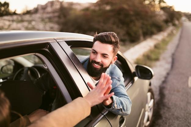 Glimlachende man hand in hand met zijn vriendin buiten auto Gratis Foto
