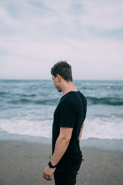 Glimlachende man in een zwart t-shirt staat aan de zanderige kust. Gratis Foto