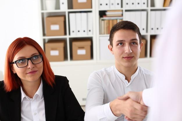 Glimlachende man in shirt shake handen hallo in kantoor Premium Foto