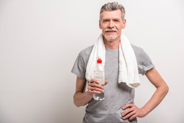 Glimlachende man in t-shirt op nek handdoek met flessenwater. Premium Foto