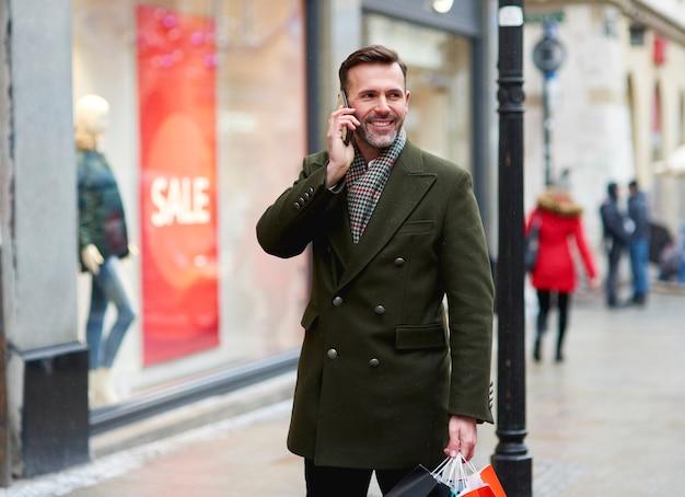 Glimlachende man is aan de telefoon tijdens het winkelen in de winter Gratis Foto