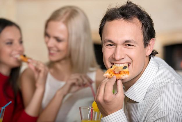 Glimlachende man is het eten van een pizza. twee meisjes praten. Premium Foto