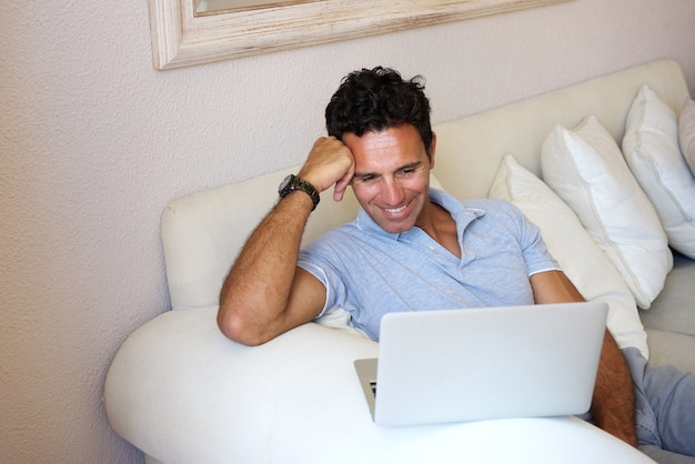 Glimlachende man om thuis te zitten met laptop Premium Foto