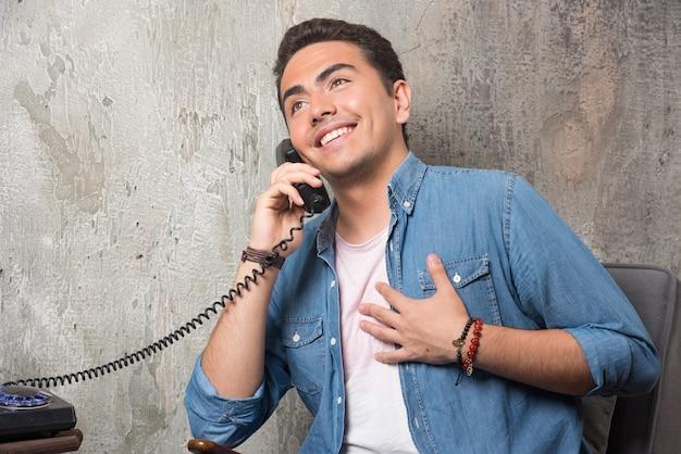 Glimlachende man praten over de telefoon en zittend op een stoel. hoge kwaliteit foto Gratis Foto