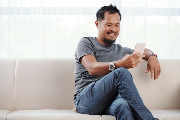 Glimlachende man zijn telefoon controleren Gratis Foto