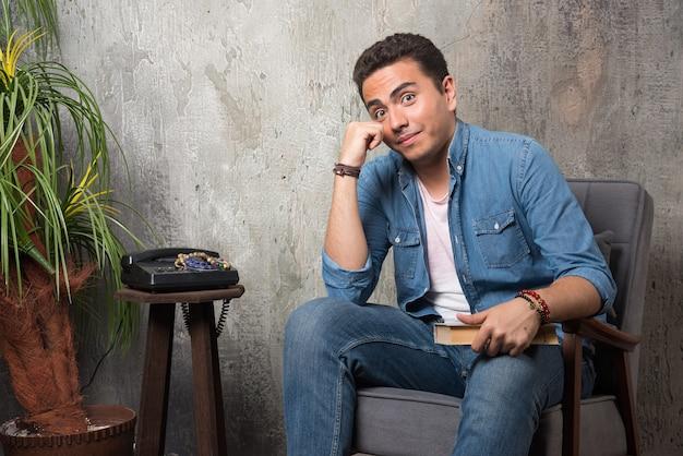 Glimlachende man zittend op een stoel met boek over marmeren achtergrond. hoge kwaliteit foto Gratis Foto