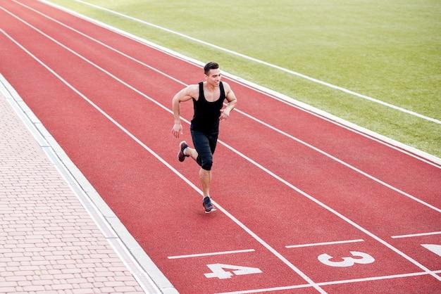 Glimlachende mannelijke atletenagent op de finishlijn Gratis Foto