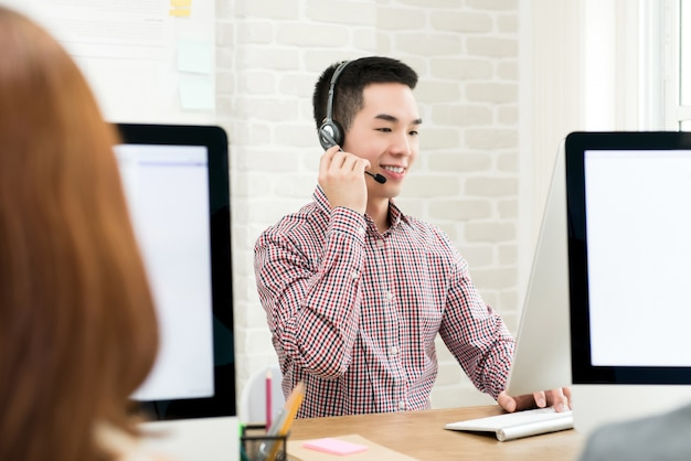 Glimlachende mannelijke aziatische telemarketingsagent in call centre Premium Foto