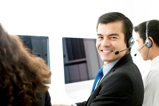 Glimlachende mannelijke klantenservice van de telemarketingsklant in call centre Premium Foto