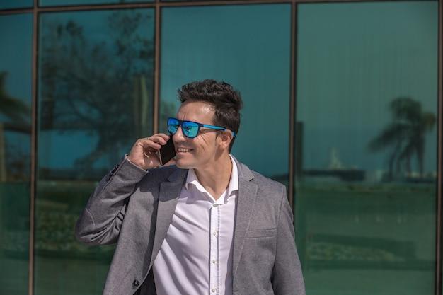 Glimlachende mannelijke ondernemer die op mobiele telefoon op straat spreekt Premium Foto