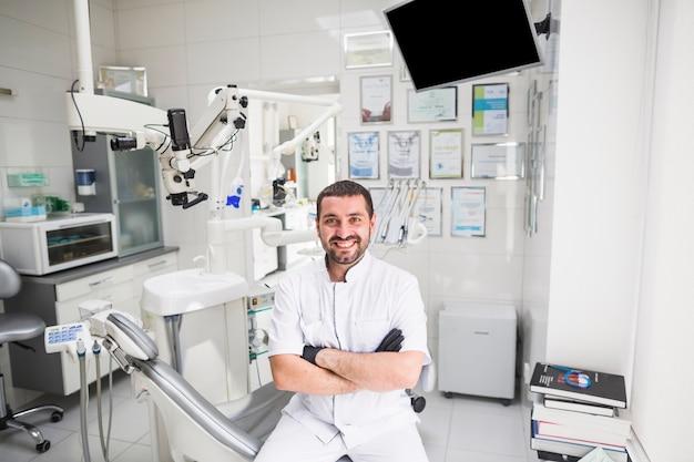 Glimlachende mannelijke tandarts die in kliniek camera bekijken Gratis Foto