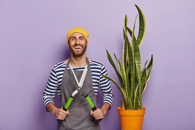 Glimlachende mannelijke tuinman houdt snoeischaar vast, geeft om slangenplant in pot, draagt hoed en schort, heeft blije uitdrukking, is professionele bloemist Gratis Foto