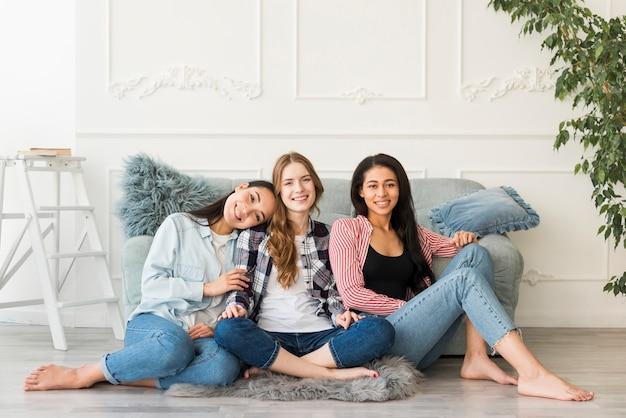 Glimlachende meisjes die op vloer met blootgestelde benen op blote voeten zitten Gratis Foto
