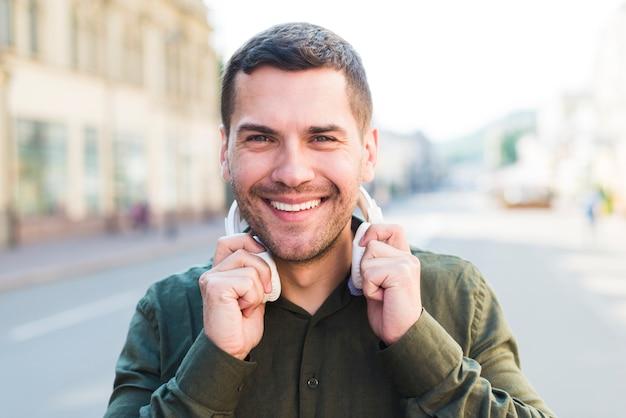 Glimlachende mens die de hoofdtelefoon van de cameraholding rond zijn hals bekijken Gratis Foto