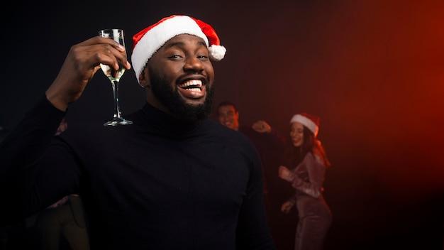 Glimlachende mens die met champagneglas nieuwe jaren toejuicht Gratis Foto