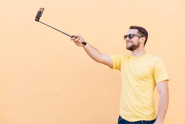 Glimlachende mens die selfie op celtelefoon nemen die zich dichtbij perzikmuur bevinden Gratis Foto
