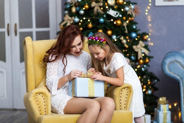 Glimlachende moeder en dochter met geschenkdoos Premium Foto