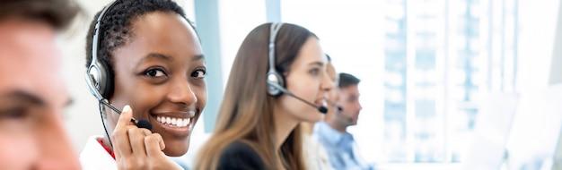 Glimlachende mooie afrikaanse amerikaanse vrouw die in call centre met divers team werkt Premium Foto