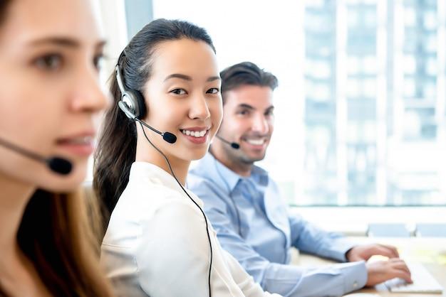 Glimlachende mooie aziatische vrouw die in call centre werkt Premium Foto