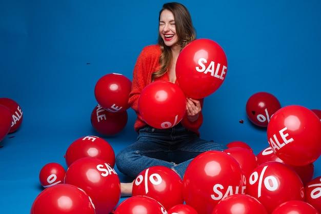 Glimlachende mooie dame met twee rode ballonnen, geïsoleerd op blauwe muur Premium Foto