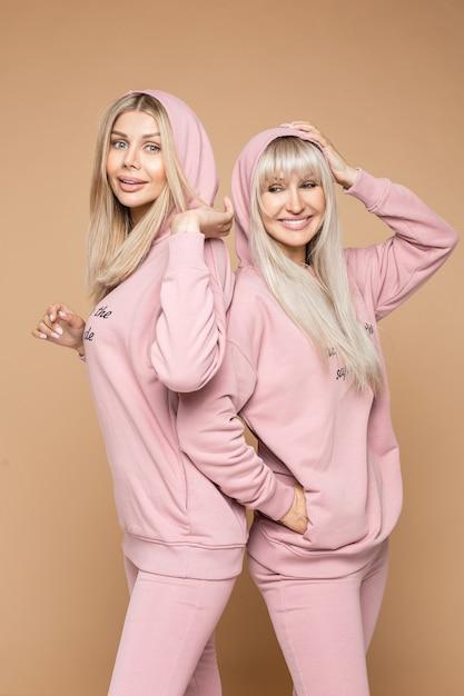 Glimlachende mooie dames die comfortabele roze sportpakken dragen terwijl ze naast elkaar staan terwijl ze naar de camera kijken, geïsoleerd op een bruine achtergrond Premium Foto