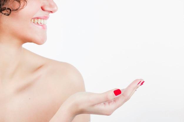 Glimlachende mooie jonge vrouw die haar hand toont tegen witte achtergrond Gratis Foto