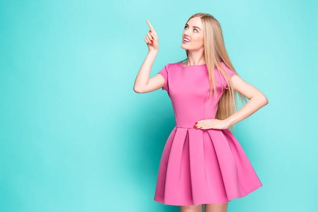 Glimlachende mooie jonge vrouw in het roze minikleding stellen, die iets voorstelt Gratis Foto