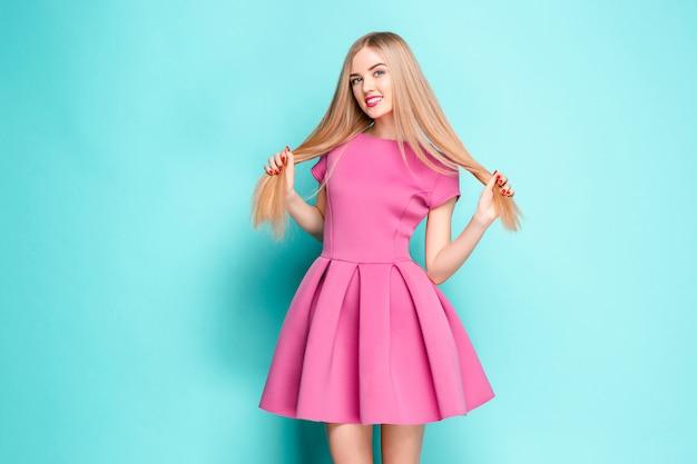 Glimlachende mooie jonge vrouw in het roze minikleding stellen Gratis Foto