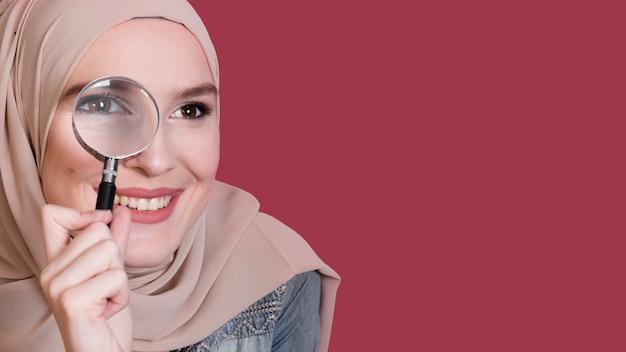 Glimlachende mooie vrouw die door meer magnifier over heldere gekleurde oppervlakte kijkt Gratis Foto