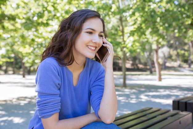 Glimlachende mooie vrouw die op mobiele telefoon in park babbelen Gratis Foto