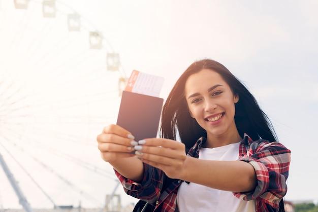 Glimlachende mooie vrouw die paspoort en luchtkaartje tonen die zich dichtbij reuzenrad bevinden Gratis Foto