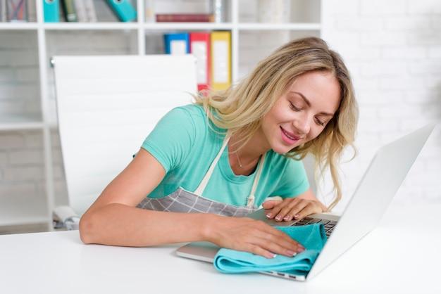 Glimlachende mooie vrouwen schoonmakende laptop met blauwe stof op wit bureau Gratis Foto