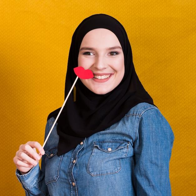 Glimlachende moslimvrouw die een document steun in de vorm van rode lippen over achtergrond houden Gratis Foto
