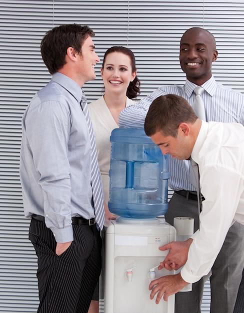 Glimlachende multi-etnische bedrijfsmensen die bij een waterkoeler interactie aangaan Premium Foto