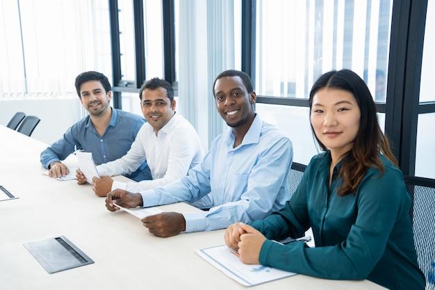 Glimlachende multi-etnische managers die met grafieken in raadsruimte werken. Gratis Foto