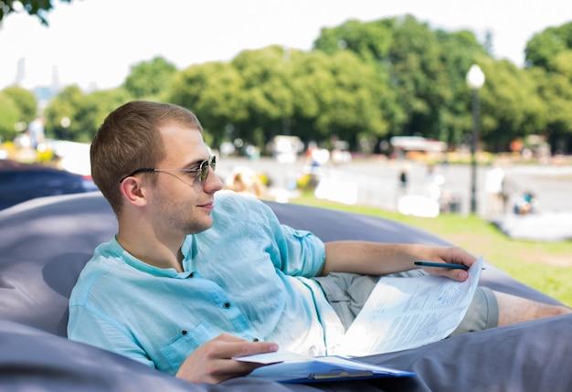 Glimlachende nadenkende jonge mens die in zonnebril op een kussen in openlucht legt, die documenten in zijn handen houdt. Premium Foto