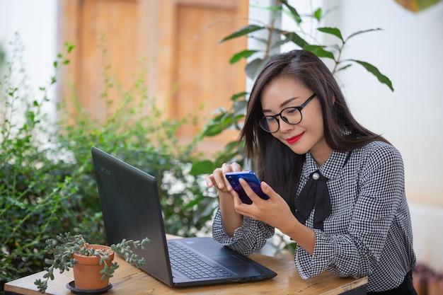Glimlachende onderneemster die aan laptop in koffie werkt Gratis Foto