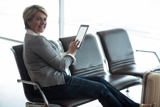 Glimlachende onderneemster die digitale tablet in wachtruimte gebruikt Gratis Foto