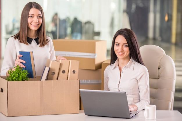 Glimlachende onderneemsters die en dozen in bureau werken inpakken. Premium Foto