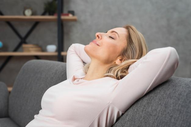 Glimlachende ontspannen jonge vrouw die haar hoofd op bank leunt Gratis Foto