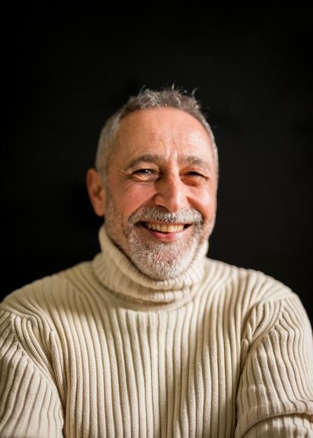 Glimlachende oude mens met grijs haar Gratis Foto