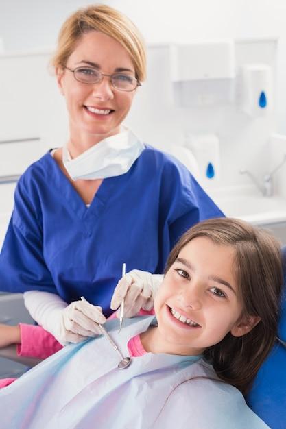 Glimlachende pediatrische tandarts met een gelukkige jonge patiënt Premium Foto
