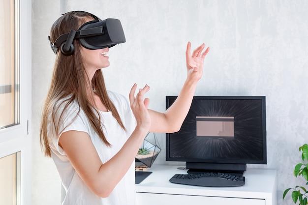 Glimlachende positieve vrouw die de hoofdtelefoon van virtuele werkelijkheidsbeschermende brillen, vr doos dragen. verbinding, technologie, nieuwe generatie, voortgangsconcept. meisje probeert objecten in virtual reality aan te raken Premium Foto