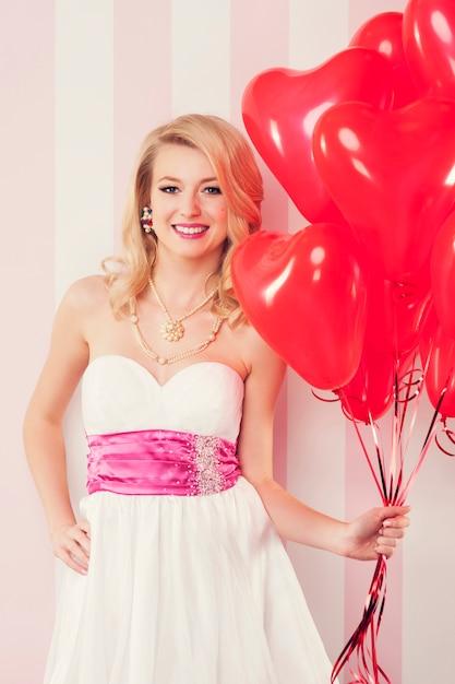Glimlachende retro vrouw met rode ballons in gevormd hart Gratis Foto