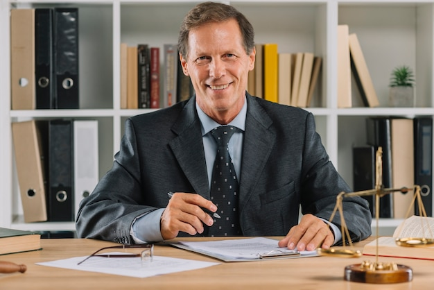 Glimlachende rijpe advocaat die in de rechtszaal werkt Gratis Foto